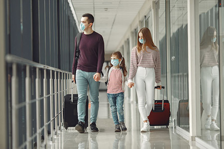 Family with Luggage Wearing Masks at Airport